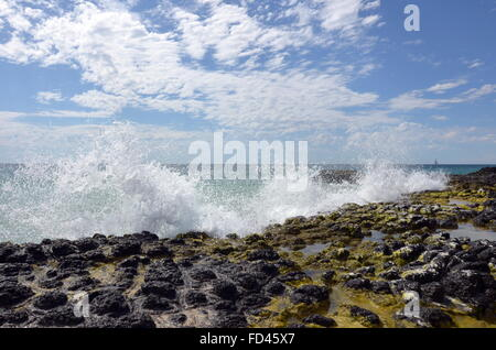 A wave splashing up against the basalt rock formations on the Back Beach near Wyalup Rocky Point at Bunbury, Western - Stock Photo