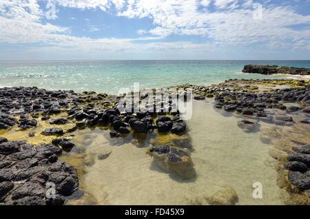 A clear rock pool on the basalt rock formations on the Back Beach near Wyalup Rocky Point at Bunbury, Western Australia - Stock Photo
