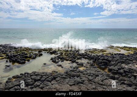 A wave splashing up against basalt rock formations on the Back Beach near Wyalup Rocky Point at Bunbury, Western - Stock Photo