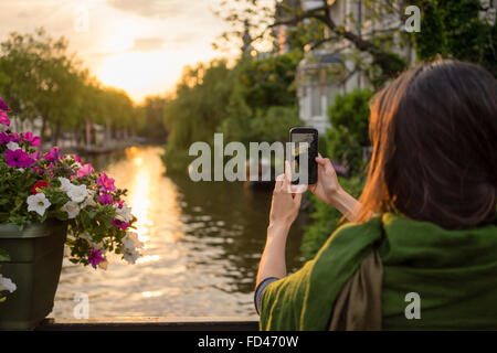 a tourist young women  in Amsterdam take pictures at a beautiful sunset on a bridge  tourist young women  in Amsterdam - Stock Photo