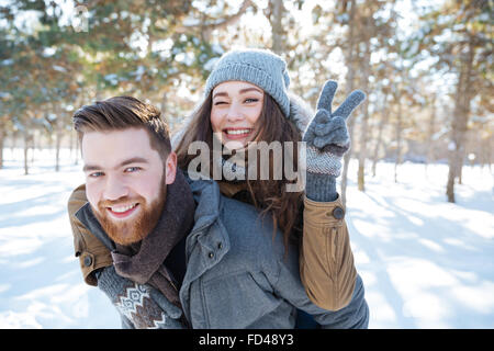 Happy young couple walking in winter park and showing victory sign at camera - Stock Photo