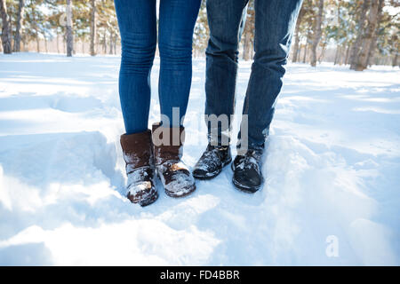 Closeup portrait of a male and female legs in jeans standing in winter park - Stock Photo