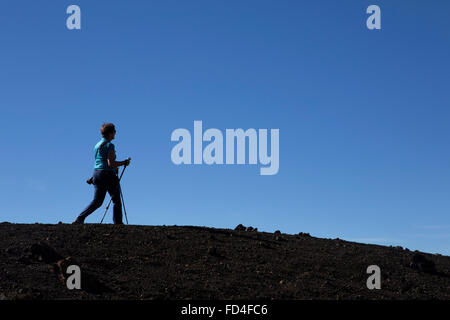 A woman Nordic walking on the ridge of the Samara Volcano in Teide National Park on Tenerife, Spain. She uses two - Stock Photo