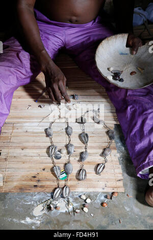 Divination in the house of the Fa in Ouidah. Rosary made of cowries. - Stock Photo