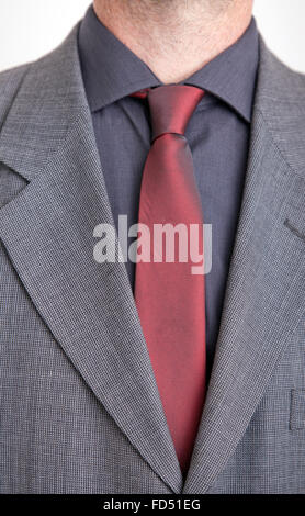 Man in suit jacket, red tie and grey shirt. - Stock Photo