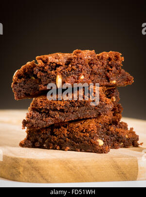 Three Chocolate Brownies stacked on a board with dark background - Stock Photo