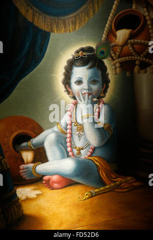 Painting in the London ISKCON hindu temple : Baby Krishna spilling butter - Stock Photo