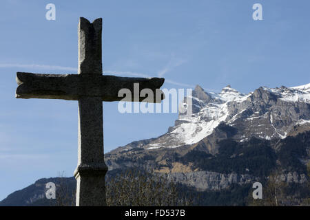 Cross. Passy cemetery. Aiguille de Varan and Col de Barmerousse. - Stock Photo