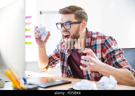 Angry crazy modern designer in glasses with beard yelling and crumpling paper on his workplace - Stock Photo