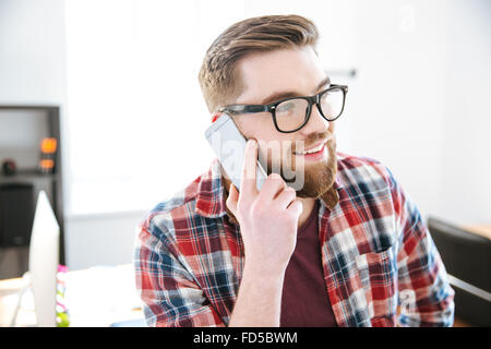 Happy attractive young man with beard in plaid shirt and glasses talking on cell phone in the office - Stock Photo