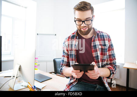 Happy handsome man with beard in plaid shirt and glasses sitting on the table in office and using tablet - Stock Photo
