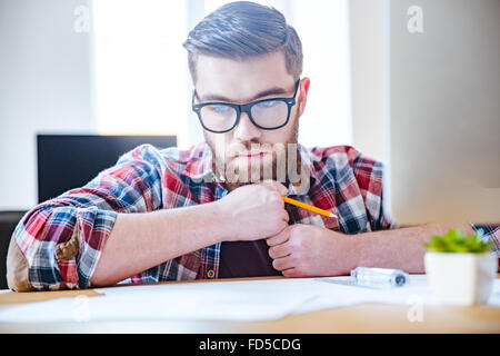 Portrait of pensive bearded young engineer in glasses sitting at the table and creating blueprint - Stock Photo