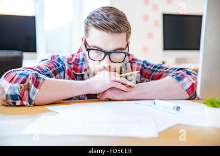 Thoughtful bearded young man in glasses working with blueprits using pencil and ruler in the office - Stock Photo