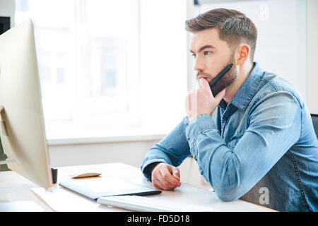 Pensive attractive bearded male designer in jeans shirt thinking and making blueprints using pen tablet - Stock Photo