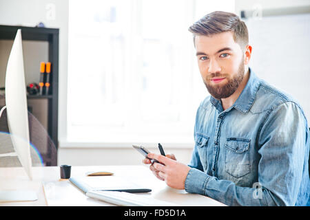 Handsome smiling bearded young man sitting on workplace in office and using mobile phone - Stock Photo