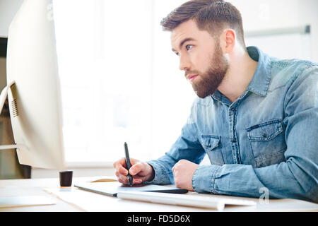 Concentrated handsome young designer with beard in blue shirt drawing using computer and graphic tablet in the office - Stock Photo