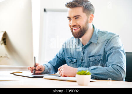 Happy attractive young male designer sitting in office and drawing on graphic tablet - Stock Photo