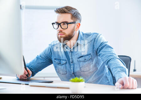 Serious concentrated young man designer drawing with graphic pen tablet using stylus in office - Stock Photo