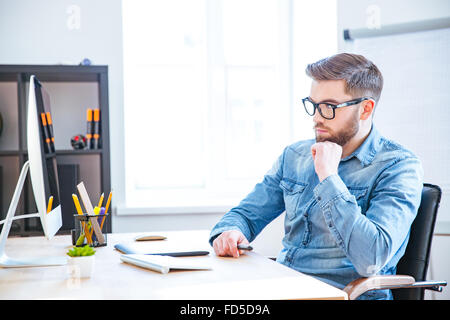 Thoughtful handsome young designer with beard in glasses using graphic tablet and computer and thinking - Stock Photo