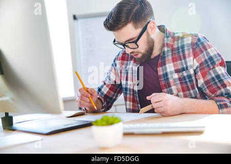 Handsome concentrated young man with beard working with blueprint using ruler and pencil in office - Stock Photo