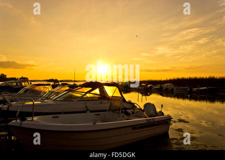 Motor Boats Moored In Row At Riverside At Sunset - Stock Photo