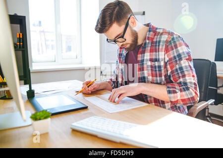 Portrait of young male designer in glasses sitting in office and making blueprint - Stock Photo