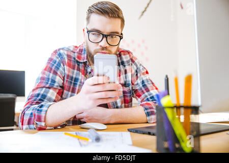 Handsome concentrated young man with beard in checkered shirt sitting at the table and using cell phone - Stock Photo