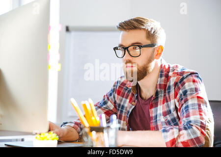 Serious handsome bearded man in checkered shirt sitting on workplace and working with computer - Stock Photo