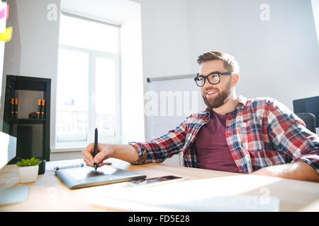 Smiling handsome young bearded designer in checkered shirt and glasses drawing and using graphic pen tablet and - Stock Photo