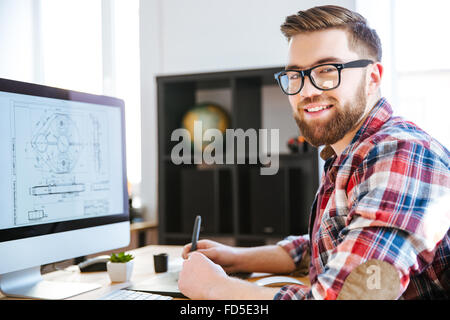 Portrait of happy handsome modern designer drawing blueprint on computer using pen tablet with stylus - Stock Photo
