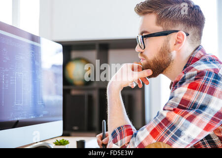 Profile of concentrated bearded man in glasses sitting and drawing blueprints on computer - Stock Photo