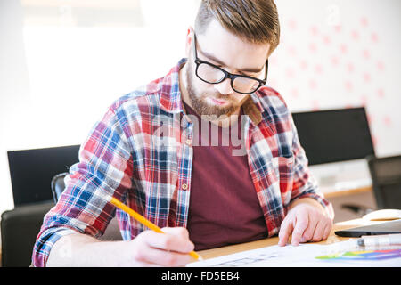 Concentrated young man with beard in plaid shirt and glasses making sketches with pencil sitting at the table - Stock Photo