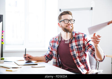 Happy handsome bearded designer using graphic pen tablet with stylus and receiving blueprints - Stock Photo