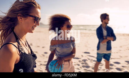 Young woman smiling and friends playing with volleyball on the beach. Young people enjoying summer vacation on the - Stock Photo