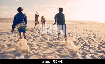 Group of young people running and competing together on a sandy beach. Young men running a race on the beach. - Stock Photo