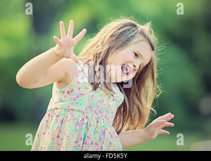 Little girl playing outside making a silly face and being expressive with her hands. - Stock Photo