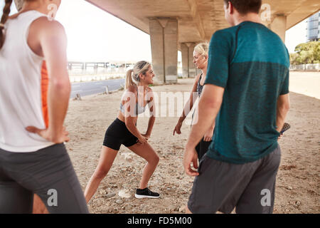 Fit young woman with running club group stretching after a run. Young people going stretching workout after a morning - Stock Photo