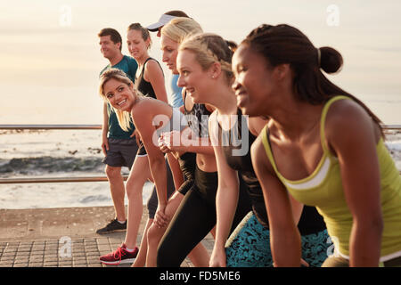 Group of young athletes in start position, focus on woman. Fit young people preparing for race along sea. - Stock Photo