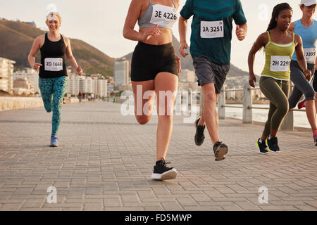 Diverse group of runners competing in a race. Athletes sprinting on a street along the sea. - Stock Photo