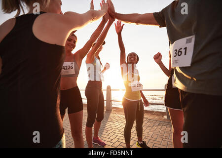 Shot of male and female runners high fiving each other after a race. Diverse group of athletes giving each other - Stock Photo