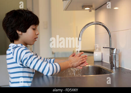 Eight year old boy washing hands in the kitchen - Stock Photo