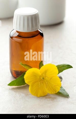 Bottle with  Evening Primrose oil and fresh flower - Stock Photo