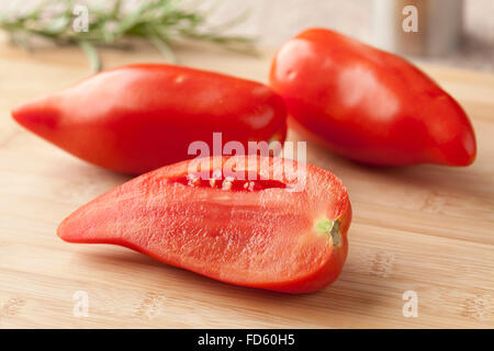 Whole and half fresh Cornue des Andes tomatoes - Stock Photo