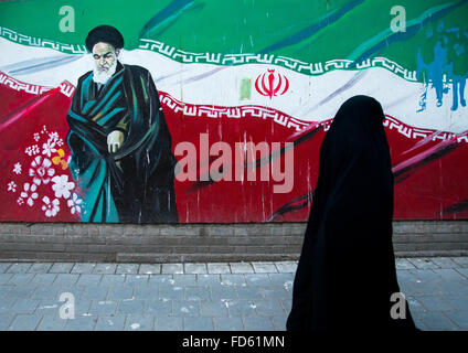 veiled woman passing in front of propaganda sign with ayatollah khomeini on the wall of the former u.s. embassy, - Stock Photo