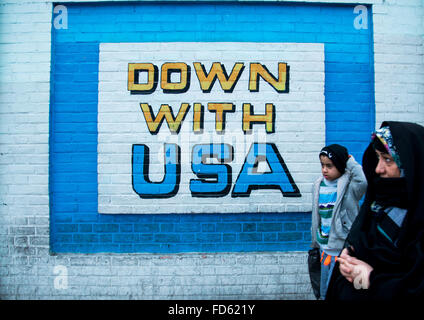people passing in front of anti-american mural propoganda on the wall of the former united states embassy, Central - Stock Photo