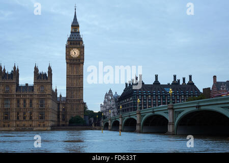 Big Ben and bridge, traffic on bridge at dusk in London, natural light and colors in the early cloudy morning in - Stock Photo