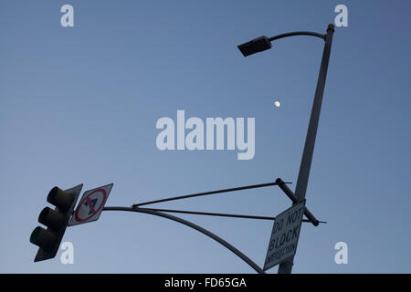 Low Angle View Of Road Sign With Street Light Against Clear Sky At Dusk - Stock Photo