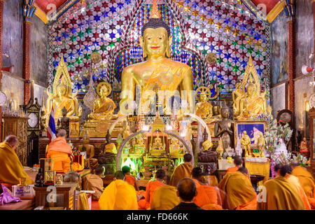 Buddhist monks perform meditation rituals during evening prayers at Wat Phra That Doi Suthep in Chiang Mai, thailand. - Stock Photo