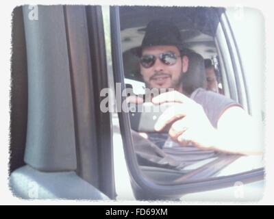 Refection Of Man Photographing Through Smart Phone On Side-View Mirror Of Car - Stock Photo