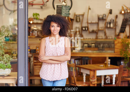 Small business owner standing in the door of her coffee - Stock Photo